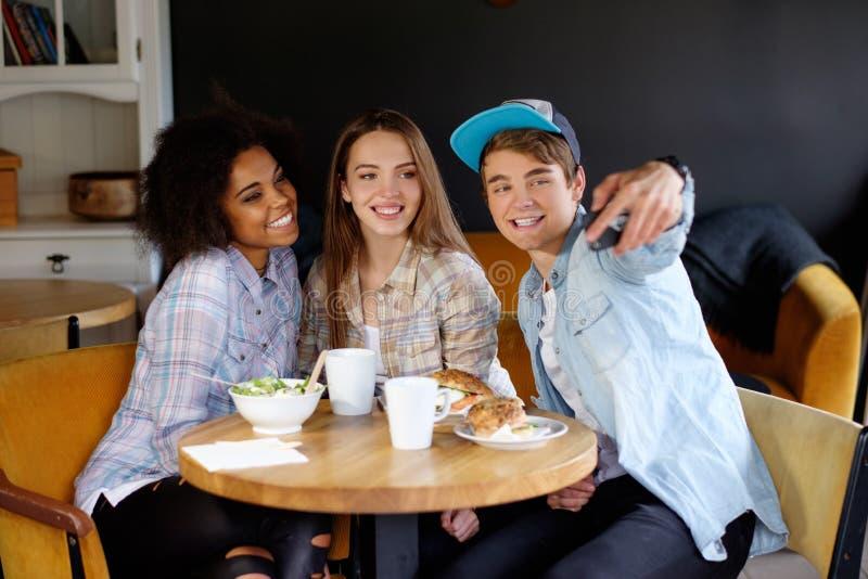 采取在咖啡馆的快乐的多种族朋友selfie 免版税库存图片