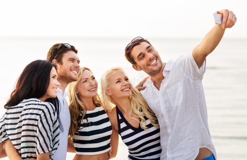 采取在夏天海滩的愉快的朋友selfie 免版税库存图片