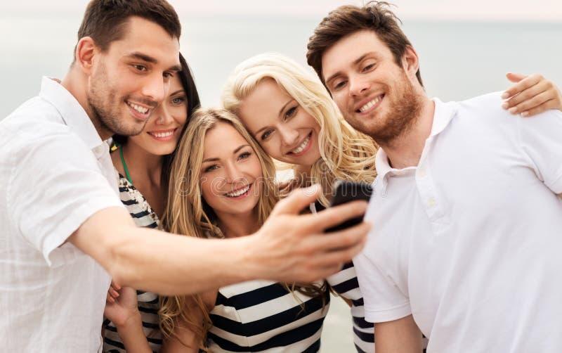采取在夏天海滩的愉快的朋友selfie 免版税库存照片