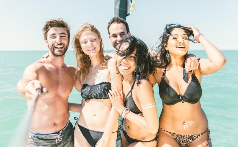采取在小船的小组朋友selfies 免版税库存照片