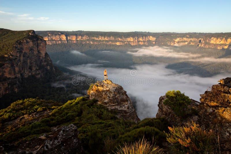 采取在山和谷宏伟的视图的徒步旅行者作为Th 免版税图库摄影