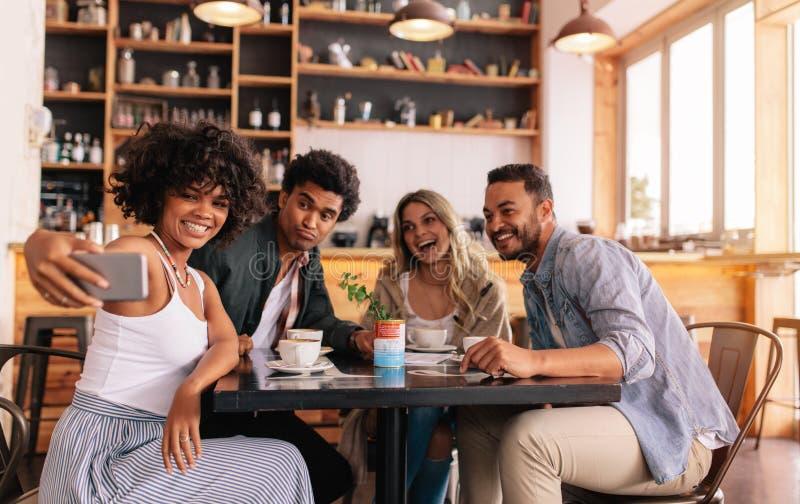 采取在巧妙的电话的不同的小组朋友selfie在咖啡馆 免版税库存图片