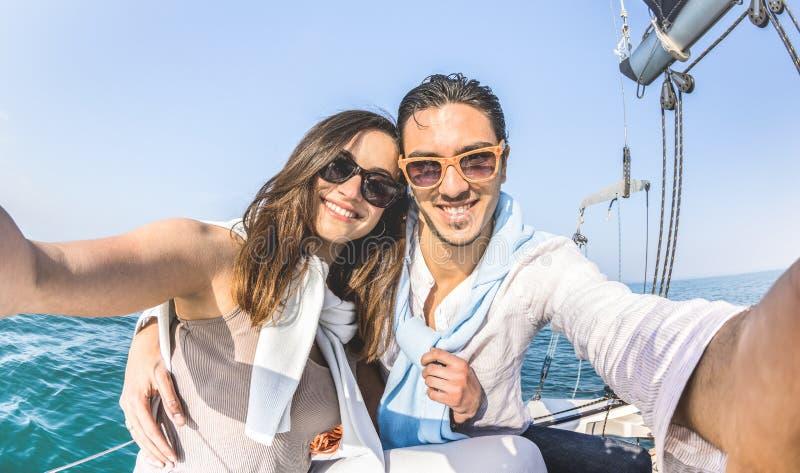 采取在帆船游览环球-爱概念的年轻恋人夫妇selfie在周年纪念在豪华风船的党巡航 图库摄影