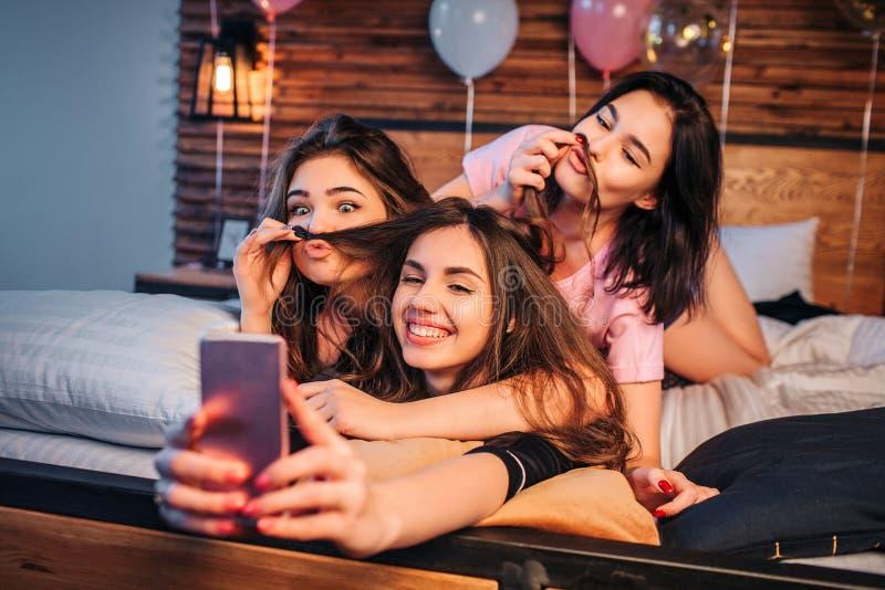采取在床上的三嬉戏的年轻女人selfie在屋子里 两个模型使用与第三个女孩的头发 他们在照相机看 库存图片