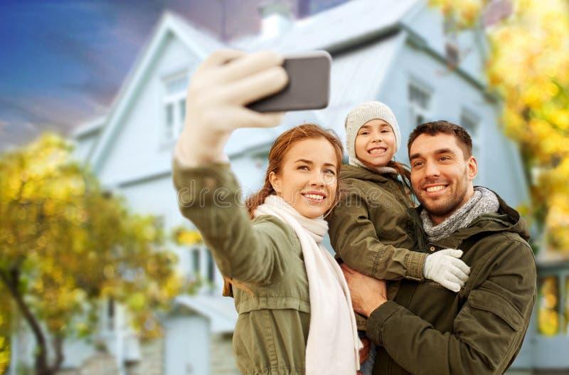 采取在房子的家庭selfie在秋天 免版税图库摄影