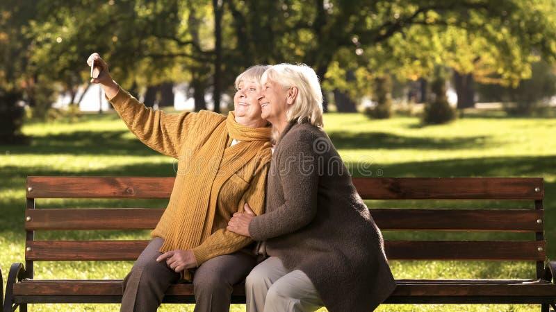 采取在手机的两个老妇人selfie坐长凳在公园技术 免版税库存图片
