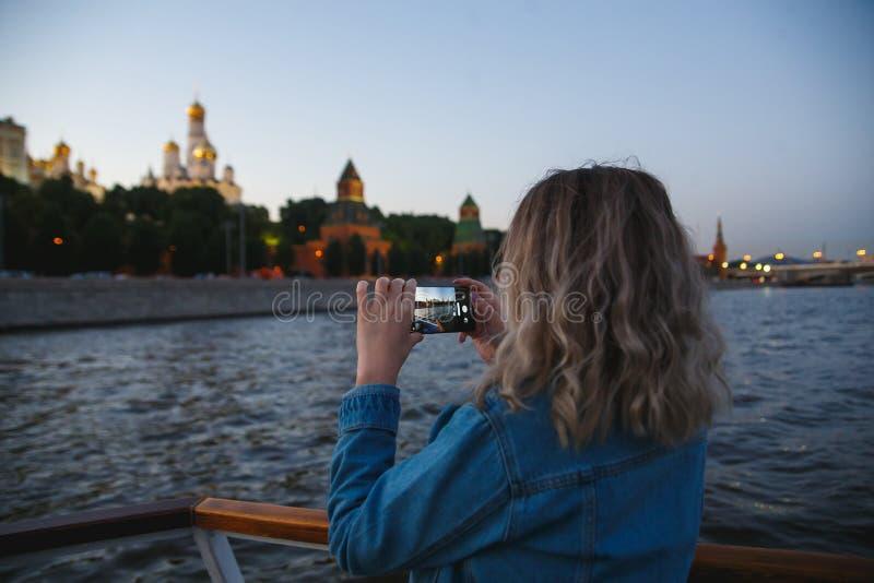 采取在手机的图片在莫斯科河的小船旅行期间背景的克里姆林宫的妇女游人 免版税图库摄影