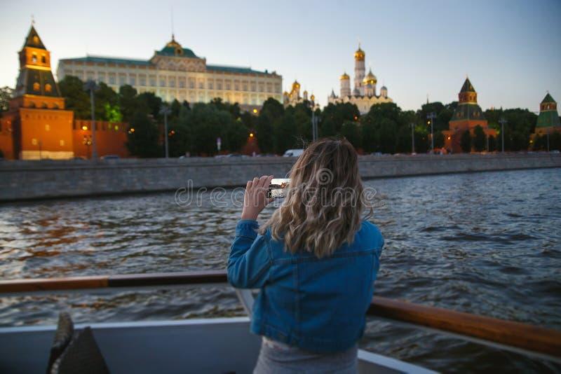 采取在手机的图片在莫斯科河的小船旅行期间背景的克里姆林宫的妇女游人 库存照片
