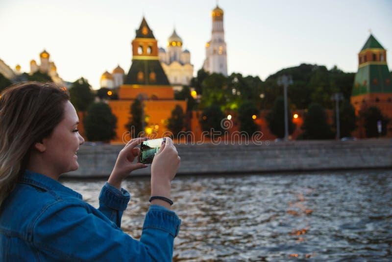 采取在手机的图片在莫斯科河的小船旅行期间背景的克里姆林宫的妇女游人 免版税库存照片