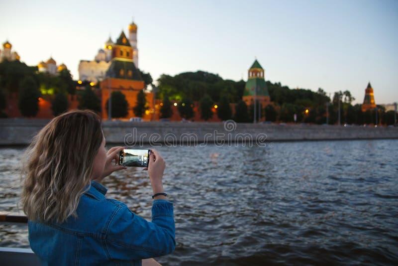 采取在手机的图片在莫斯科河的小船旅行期间背景的克里姆林宫的妇女游人 免版税库存图片