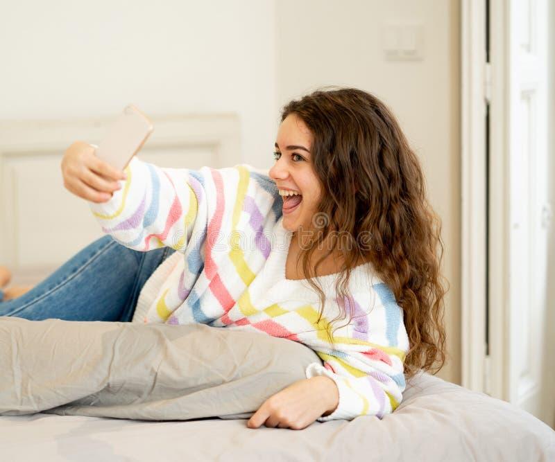 采取在手机的年轻美丽的少年女孩selfie为 库存照片