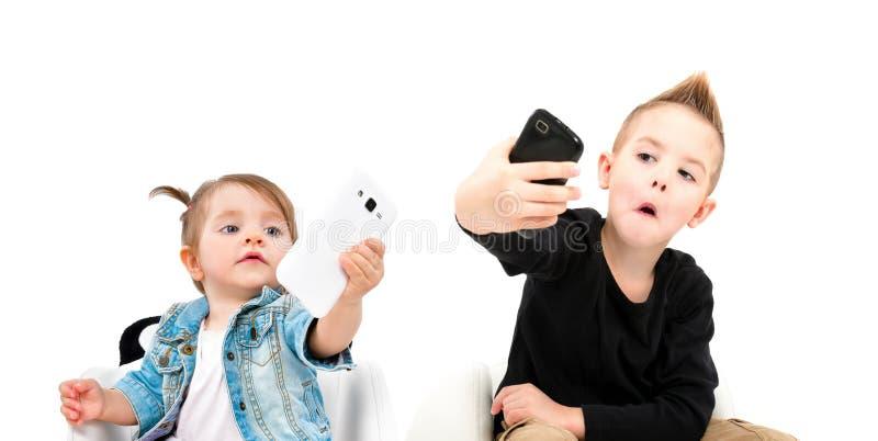 采取在手机的快乐的男孩和逗人喜爱的女孩画象selfie 图库摄影