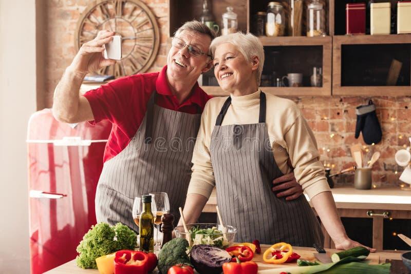 采取在手机的资深夫妇selfie在厨房里 图库摄影