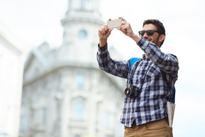 采取在旅行的年轻人智能手机Selfie 库存图片