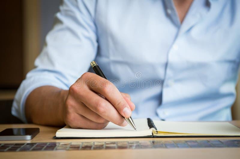 采取在日志的笔记下的人 免版税库存照片