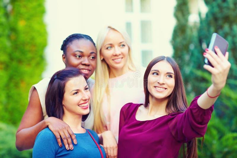 采取在智能手机的小组多种族女孩selfie 库存照片