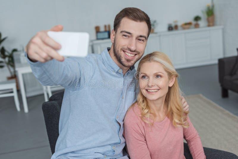 采取在智能手机的微笑的母亲和增长的儿子画象selfie 库存照片