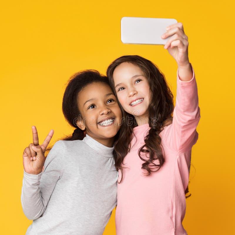 采取在智能手机的最好的朋友selfie,获得乐趣 免版税库存图片