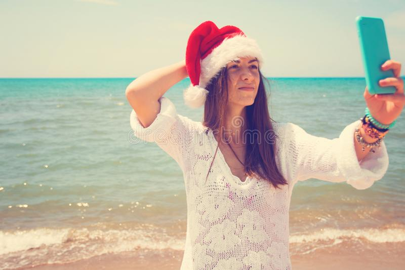 采取在智能手机的红色圣诞老人帽子的圣诞节年轻微笑的妇女图片自画象在海背景的海滩 定调子 库存照片
