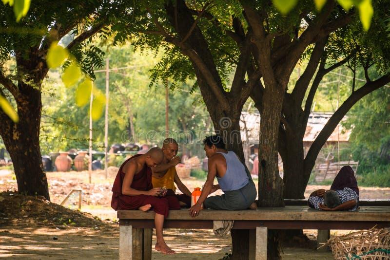 采取在树下的修士和人们 蒲甘,缅甸,2018年8月11日 库存图片