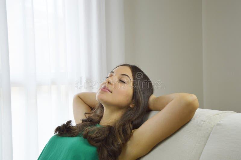 采取在沙发的轻松的少妇休息 有绿色无袖衫在家放松的微笑的少妇在沙发坐沙发  免版税图库摄影