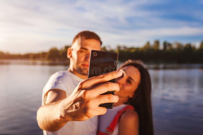 采取在河岸的愉快的年轻夫妇selfie在日落 获得的妇女和的人乐趣 智能手机特写镜头  库存图片
