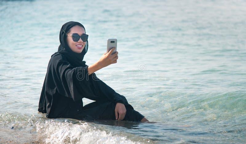 采取在海滩的回教妇女selfie 库存照片