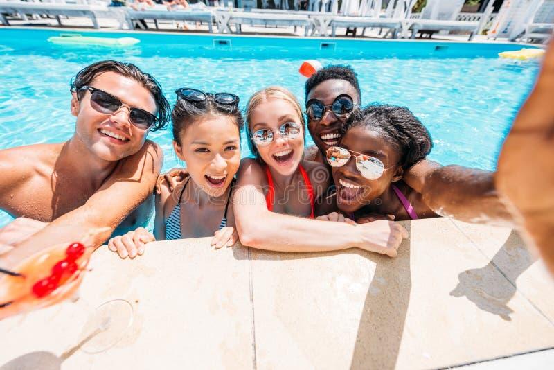 采取在游泳的小组年轻愉快的不同种族的人民selfie 免版税库存照片
