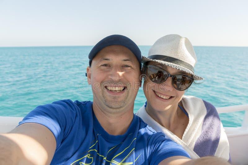 采取在游艇的愉快的中间年迈的夫妇selfie 采取在游艇甲板的美好的愉快的夫妇selfie漂浮在海 航行, 免版税库存照片