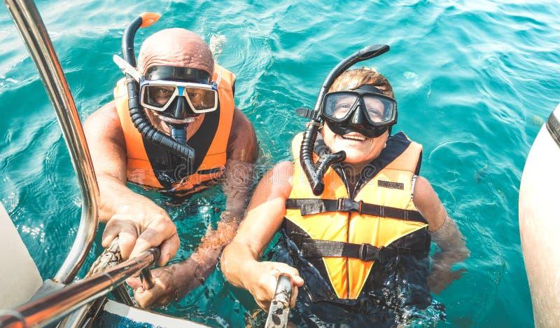 采取在热带海游览的退休的夫妇愉快的selfie与救生背心和废气管面具-潜航小船的旅行 免版税库存图片