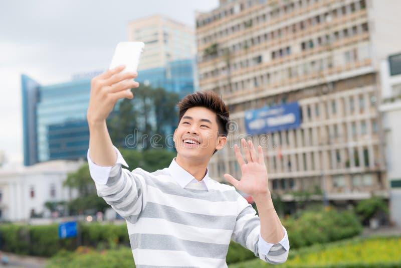 采取在现代智能手机的快乐的亚裔人selfie,当享受宜人的步行在公园,被射击时的画象 库存图片