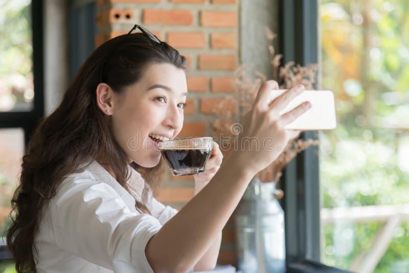 采取在电话的女商人selfie在咖啡休息时间在她的职场 免版税库存照片