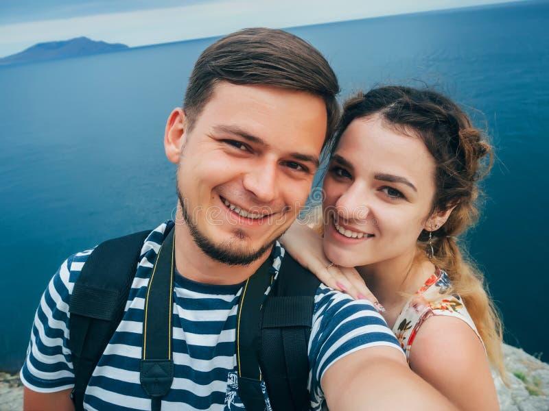 采取在电话的愉快的微笑的夫妇旅客一selfie对休息反对海 图库摄影