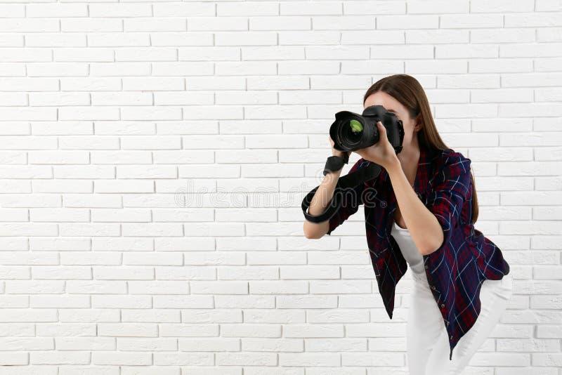 采取在白色砖墙附近的专业摄影师 r 免版税图库摄影
