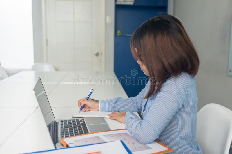 采取在笔记本的年轻女实业家笔记在办公室 图库摄影