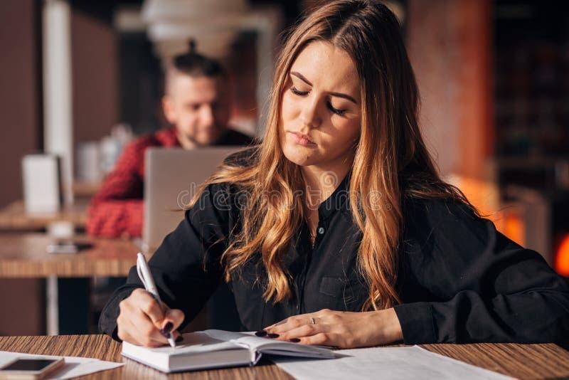 采取在笔记薄的女实业家笔记坐在咖啡馆 免版税库存照片