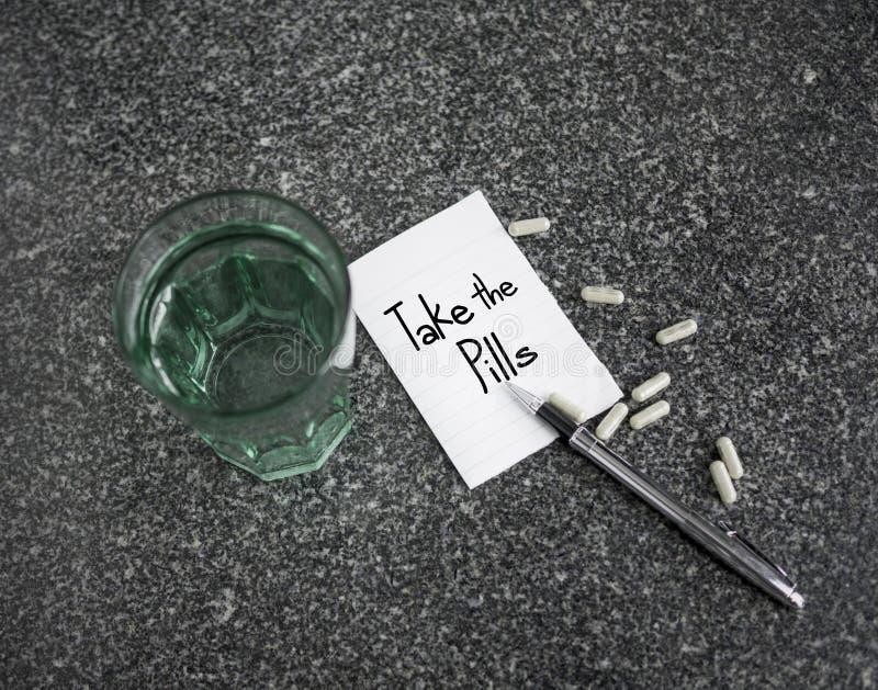 采取在纸笔记的药片文本与医学和杯水 库存图片