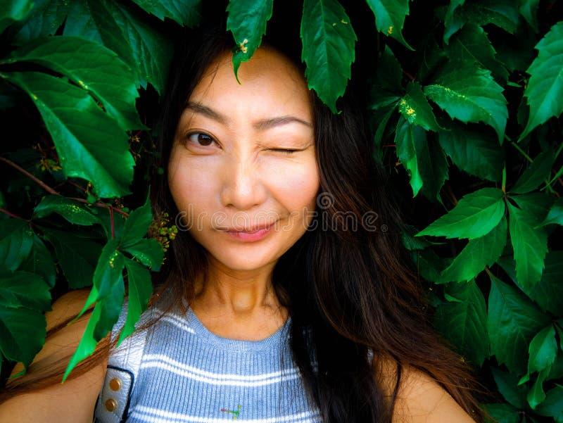 采取在绿色葡萄叶子背景的一个逗人喜爱的亚裔女孩的画象selfie 免版税图库摄影
