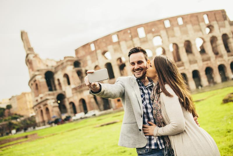 采取在罗马斗兽场前面的年轻夫妇selfie在罗马,意大利 图库摄影