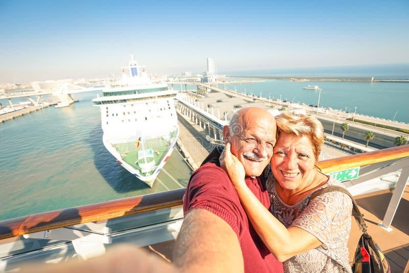 采取在船的资深愉快的夫妇selfie在巴塞罗那港口 库存照片