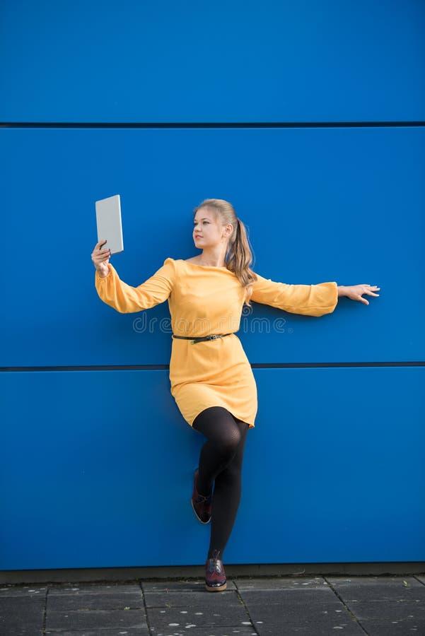 采取在蓝色背景的少妇selfie 免版税图库摄影