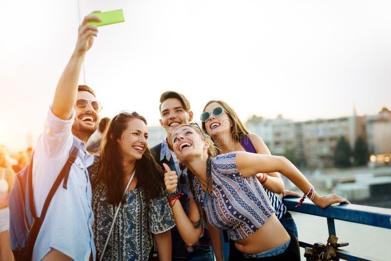 采取在街道上的愉快的年轻朋友selfie 图库摄影