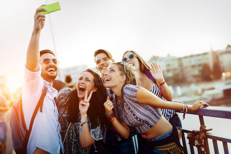 采取在街道上的愉快的年轻朋友selfie 库存图片