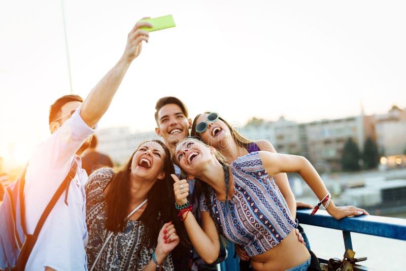 采取在街道上的愉快的年轻朋友selfie 免版税图库摄影