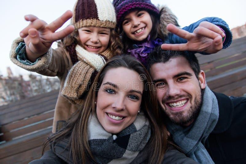 采取在街道的愉快的年轻家庭一selfie 免版税库存图片