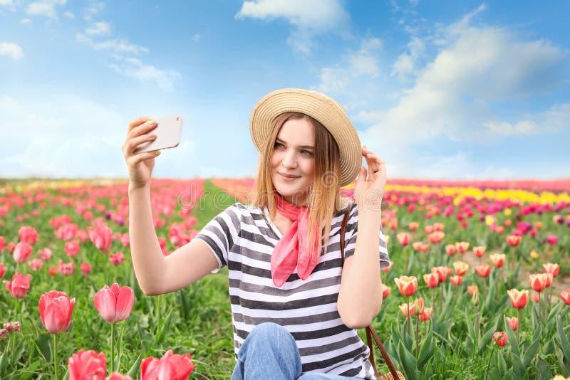 采取在郁金香领域的美丽的年轻女人selfie在春日 免版税库存图片