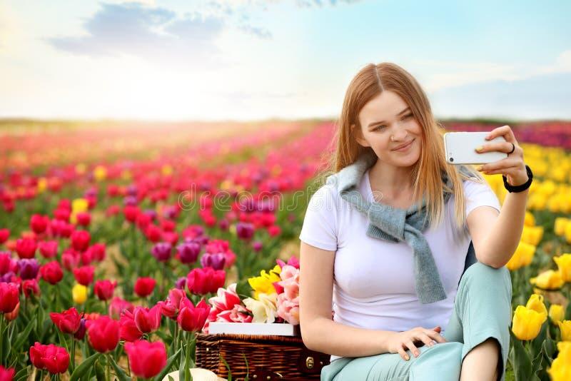 采取在郁金香领域的美丽的年轻女人selfie在春日 库存照片