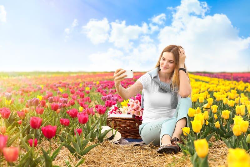 采取在郁金香领域的美丽的年轻女人selfie在春日 免版税库存照片