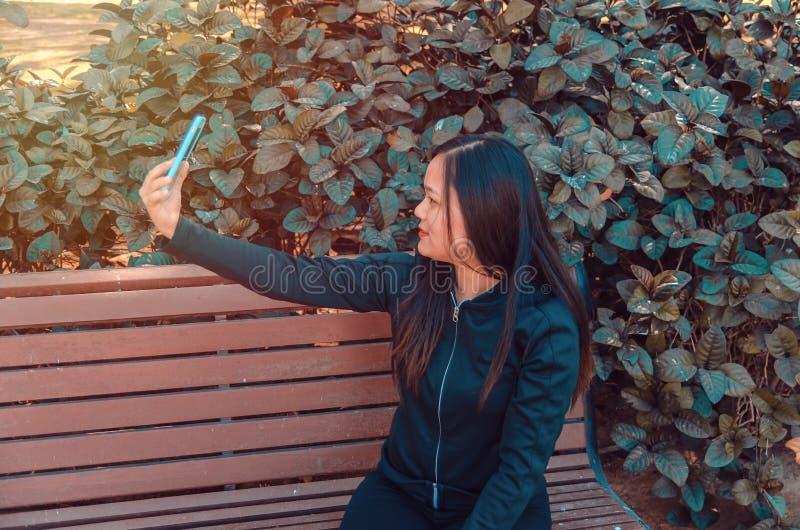 采取在长凳的夫人selfie使用她巧妙的电话 库存图片