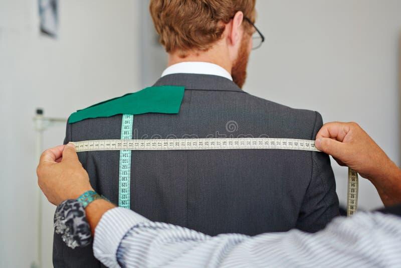 收回从客户的老裁缝测量在小工作室演播室做衣服夹克 照片拍摄时间